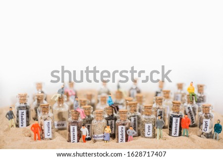 Glass test-tube with sand of different summer vacation destinations. Located in sand with small people figures. #1628717407