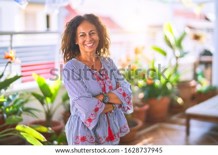 Middle age beautiful woman smiling happy and confident standing with a smile on face at terrace #1628737945