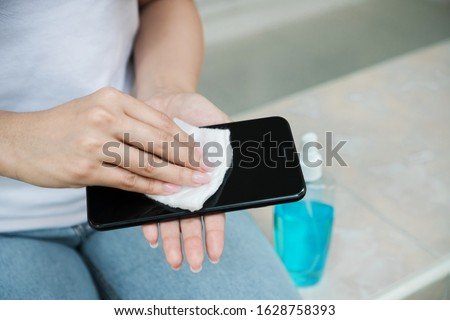 Woman cleaning smartphone screen with alcohol on white background. Concept of Cleaning dirty screen phone for disease prevention from bacteria.  #1628758393