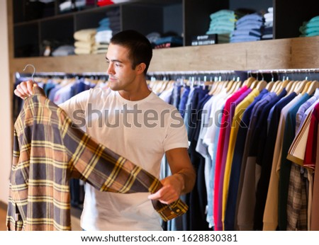 Man buys checkered shirt in the fashion store #1628830381