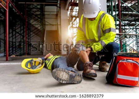 First aid support accident at work of construction worker at site. Builder accident falls scaffolding on floor, Safety team helps employee accident. #1628892379