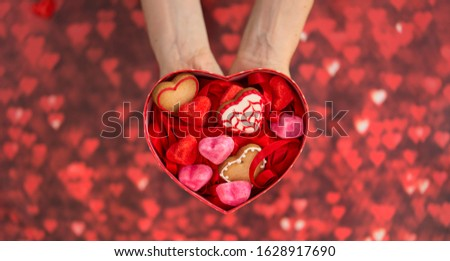 heart-shaped box, with heart-shaped jelly beans, heart-shaped cookies and red background #1628917690