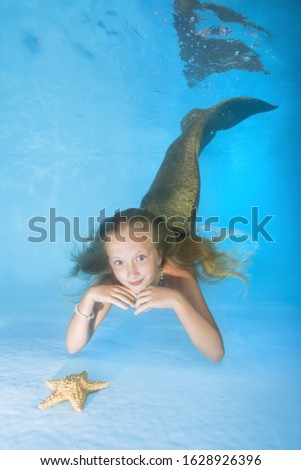 Young beautiful mermaid looks at a starfish and smiling underwater in swimming pool. underwater girls pictures