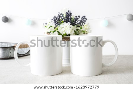 Two blank white 11oz coffee mugs side by side in kitchen setting on white background, friendship mugs mockup