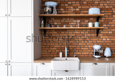 Kitchen in a contemporary shaker style with pastel blue kitchen appliances and orange cooker and the hood. Brick wall backsplash and retro style accessories. Shaker style kitchen.  #1628989153