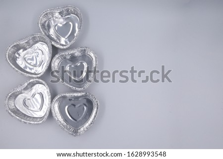 Aluminum baking tins in the form of hearts are placed on the right, and the rest is empty for placing text. #1628993548