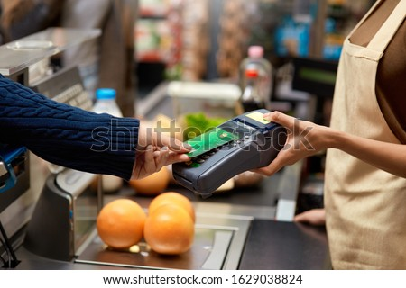 Cropped view of young adult man holding plastic credit card in hand, using terminal and paying for shopping in supermarket #1629038824