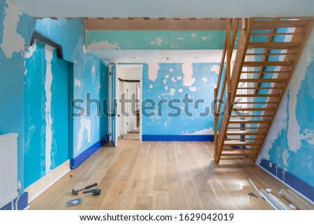 Room home improvement with a new wooden floor and walls prepared for painting #1629042019