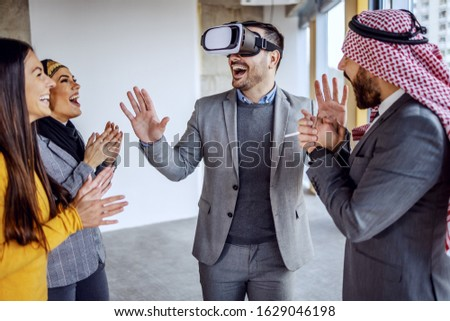 Real estate agent having vr goggles and having virtual presentation of building he standing in. Around him arab investors and his colleague clapping. #1629046198