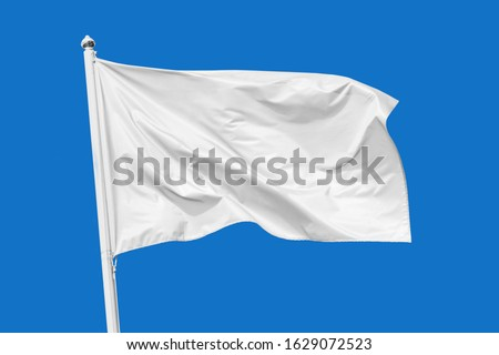 White flag waving in the wind on flagpole, isolated on blue background, closeup Royalty-Free Stock Photo #1629072523