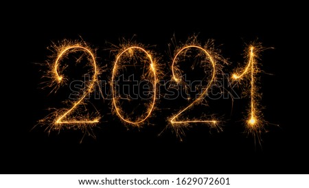 Happy New Year 2021 written with bengal fire, sparkler fireworks candle isolated on a black background. New Year dark background.