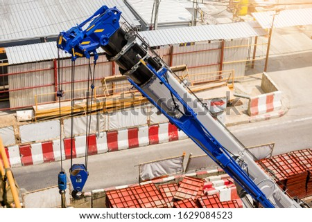 Blue crane boom with hooks and sling cable at construction site. Boom of mobile crane. #1629084523