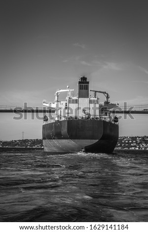 A black and white picture of a large cargo ship passing by under the Bosphorus Bridge in Istanbul shot taken from the back of the ship.