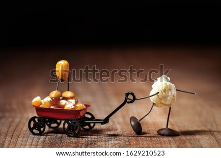 funny popcorn figure is moving a handcart with a corn figure, concepts like Father's Day or playing with the kids Royalty-Free Stock Photo #1629210523