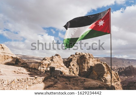 The flag of Jordan blowing in the wind in Petra, Jordan. Three-color flag of Jordan on the background of rocks and mountains in the Jordan desert. Copy space. #1629234442
