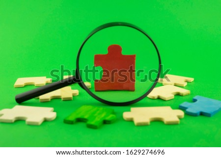 Colorful jigsaw puzzle pieces with magnifying glass focused on a single red corner piece in a conceptual image over green for search, investigation and problem solving #1629274696