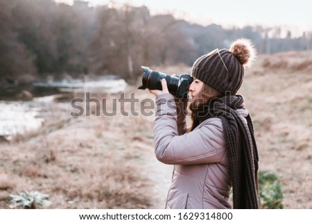 Female photographer talking pictures outdoor with camera. Nature photography