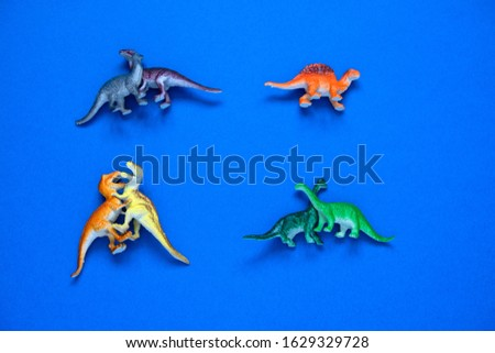 top view small plastic dinosaurs couples and one lonely dinosaur on a blue background