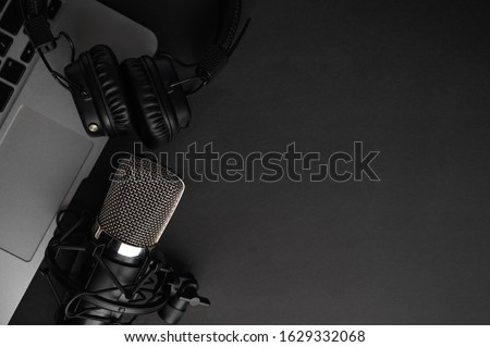 Studio black studio microphone with studio headphones on a laptop on a black background. Banner. Radio, work with sound, podcasts, blogging.