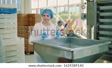 Candy factory. Factory worker checking packing machine. Young woman in uniform inspecting packing machine while working in confectionery factory. #1629389140