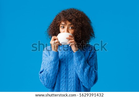 Girl listening to fresh gossips and sipping tea. Intrigued and relaxed good-looking african american woman having girlfriends meeting, drinking coffee from cup and looking camera interested #1629391432