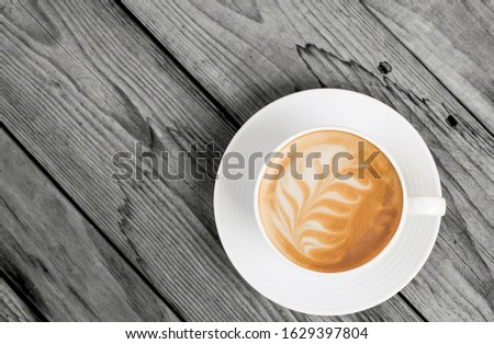 hot latte coffee photography in vintage white coffee cup set with latte art coffee flat lay top view on the dark grey retro wooden background texture with copy space feel calm and relax in the morning