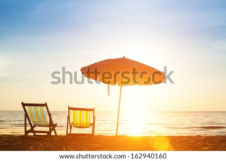 Pair of beach loungers on the deserted coast sea at sunrise. #162940160