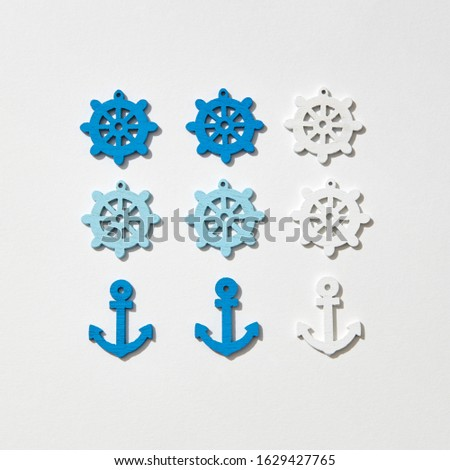 Ship anchors and wheel different colors pattern on a light grey background with hard shadows, copy space. Flat lay