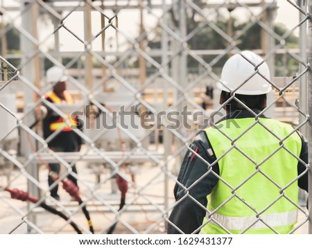 Workers, wearing personal protective equipment for safety issue, work on electrical equipement installation site (Selective focus on fence) #1629431377