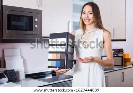 Smiling salesgirl of home furnishing store demonstrating variants of stone for kitchen countertop #1629444889