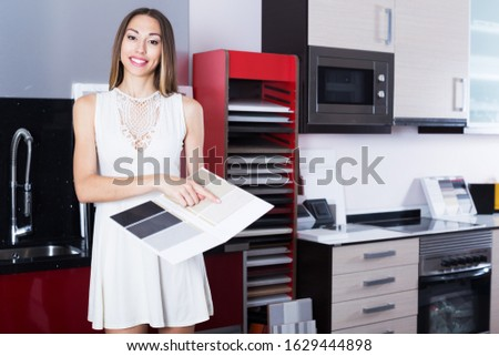 Positive woman looking for new kitchen tabletop in home furnishing salon #1629444898