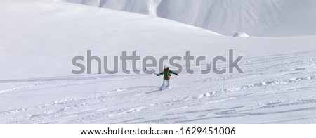 Snowboarder downhill on snowy off piste slope with newly-fallen snow at high winter mountains. Caucasus Mountains. Georgia, region Gudauri. Panoramic view. #1629451006
