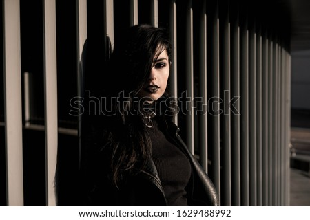 Girl in black with black aggressive make up with is standing behind white striped wall in a city. Might be a picture representing subculture, youth, teenagers, evil, protest