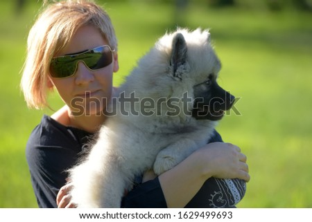 young blonde woman in summer sunglasses with keeshond wolfspitz puppy on a background of green grass #1629499693
