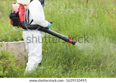 Worker spraying insecticide in the field #1629510493