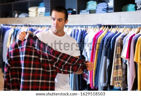 Man buys checkered shirt in the fashion store #1629518503