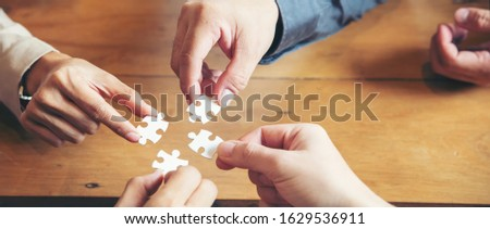 Hand of Business people holding piece of jigsaw puzzle to solution problem during brainstorming meeting -panoramic banner for web header. collaborate with Professional Businessman and Partnership.