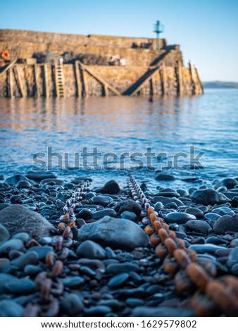 Huge rustic chains leading out into the sea. Taken in Clovelly harbour in North Devon, England.  Royalty-Free Stock Photo #1629579802