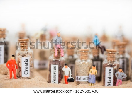 Glass test-tube with sand of different summer vacation destinations. Located in sand with small people figures. #1629585430
