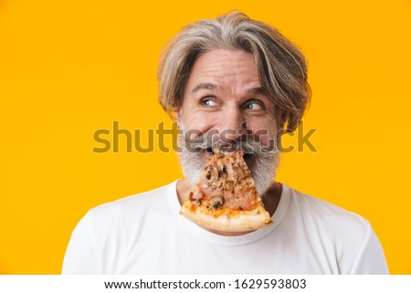 Photo of positive funny senior grey-haired bearded man posing isolated over yellow wall background eat pizza. #1629593803