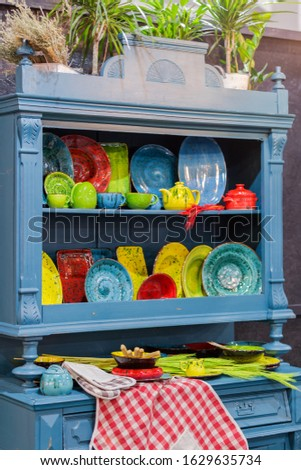 A vintage kitchen blue sideboard filled with colored dishes, plates, cup dishes and miscellaneous kitchen utensils. Beautiful decorative dishes. #1629635734