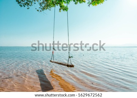 Swings under the shade of trees and tranquil seaside beaches Royalty-Free Stock Photo #1629672562