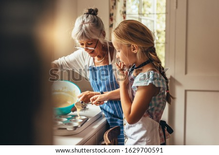 Grandmother teaching kid to make cup cakes. Happy grandmother and kid pouring cake batter in cup cake moulds. #1629700591