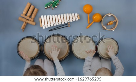 Boy girl kids playing orff instruments - Musical instruments for children: drums, flute, metallophone  Royalty-Free Stock Photo #1629765295