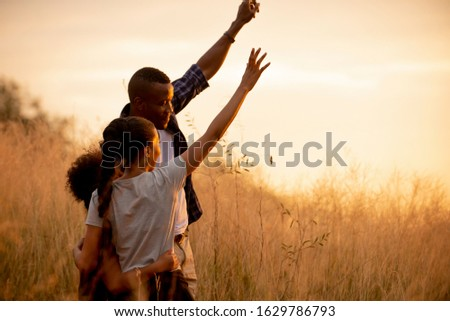 Happy african family enjoy together on meadow with sunlight at nature park , Travel  summer holiday lifestyle healthy concept