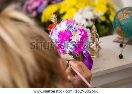 A young blond woman is writing a note on a floral arrangement. The arrangement is made of white, purple and pink chrysanthemums placed in a wooden bark box. #1629802666