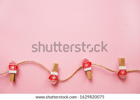 Christmas decorations decorative background. Decorative pins in the form of red gloves on a pink background. Top view, minimalism, flat lay. #1629820075