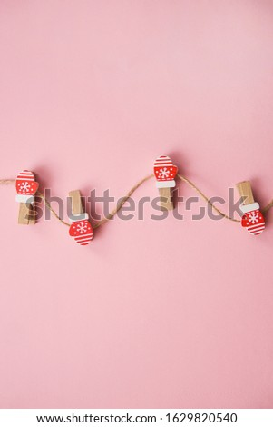 Christmas decorations decorative background. Decorative pins in the form of red gloves on a pink background. Top view, minimalism, flat lay. #1629820540