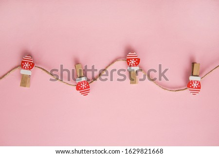 Christmas decorations decorative background. Decorative pins in the form of red gloves on a pink background. Top view, minimalism, flat lay. #1629821668