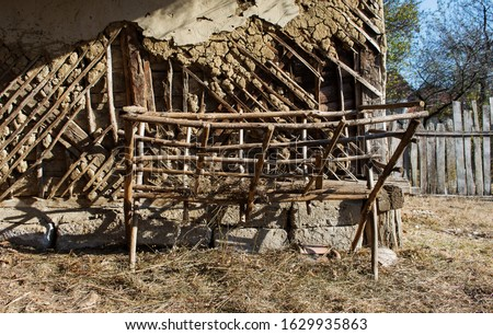 Wooden empty feeding rack. Manger feeder. Hay rack. Place for feeding the animals on the farm in the yard. Season of the autumn. Manger hay. Broken wall background made of wood and earth   #1629935863